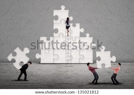 Business team work  building puzzle symbolizing working together finding  solutions to a problem - stock photo