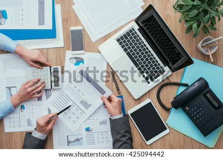 Business team working at office desk and analyzing financial reports, finance and accounting concept, top view - stock photo