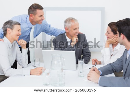 Business team working happily together on laptop in the office - stock photo