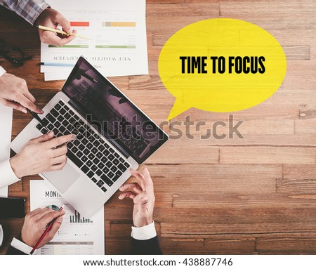 BUSINESS TEAM WORKING IN OFFICE WITH TIME TO FOCUS SPEECH BUBBLE ON DESK - stock photo