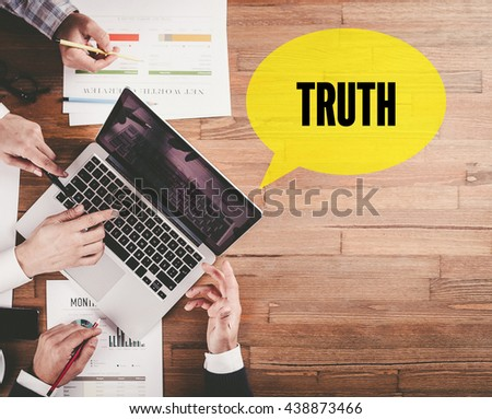 BUSINESS TEAM WORKING IN OFFICE WITH TRUTH SPEECH BUBBLE ON DESK - stock photo