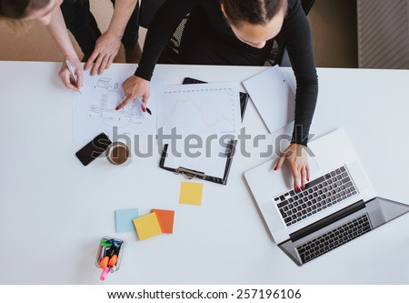 Business team working on a new plan with laptop. Top view of two young women executives working together with laptop and taking notes. - stock photo