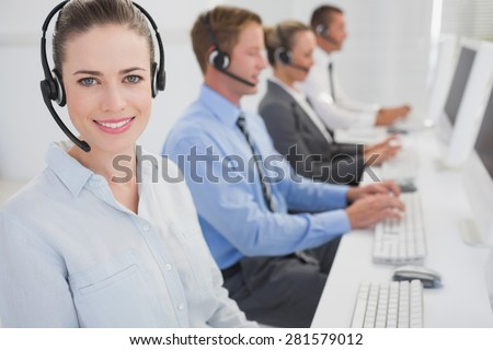 Business team working on computers and wearing headsets in call center - stock photo