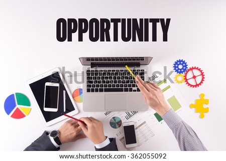 Business team working on desk with a single word OPPORTUNITY - stock photo
