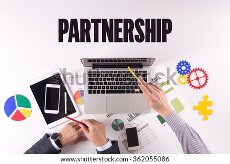 Business team working on desk with a single word PARTNERSHIP - stock photo
