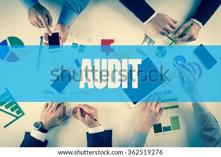 Business team working on desk with AUDIT word - stock photo