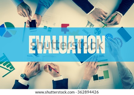 Business team working on desk with EVALUATION word - stock photo
