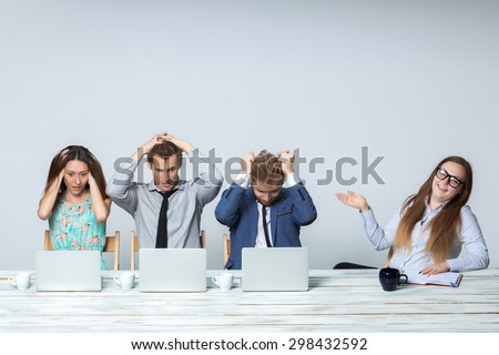 Business team working on their business project together at office on light gray background. all all grabbed his head. boss laughing. copyspace image.  - stock photo