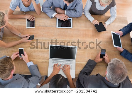 Business team working on their multimedia devices in the office - stock photo