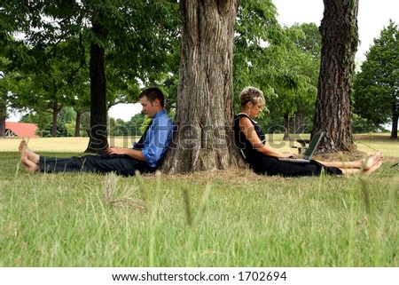 Business team working outdoors with laptops; leaning against tree