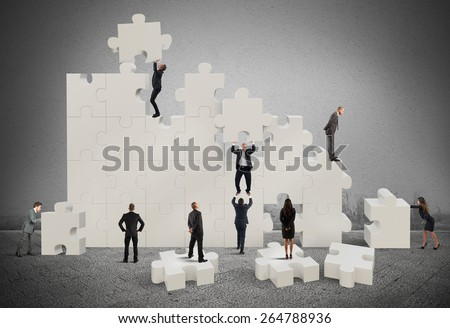 Business team working to build a puzzle - stock photo