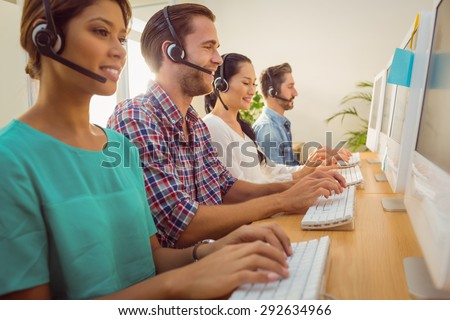 Business team working together at a call centre wearing headsets - stock photo