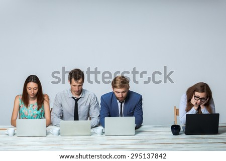 Business team working together at office on light gray background. all working on laptops. copyspace image - stock photo