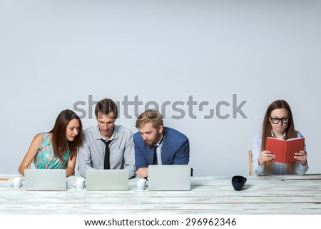 Business team working together at office on light gray background. all working on laptops. boss reading notebook. copyspace image - stock photo
