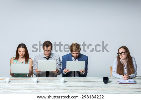 Business team working together at office on light gray background. all working on laptops. boss watching  the process. copyspace image - stock photo