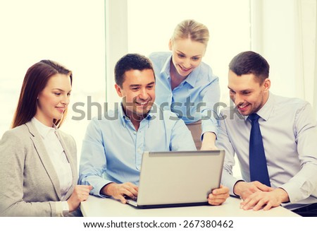 business, teamwork and office concept - smiling business team working with laptop computer in office - stock photo