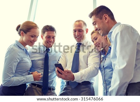 business, teamwork, people and technology concept - business team looking to smartphone in office - stock photo