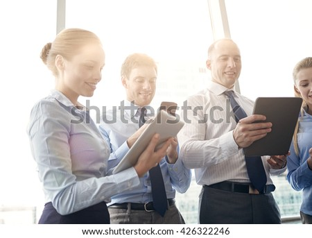 business, teamwork, people and technology concept - business team with tablet pc and smartphones in office - stock photo