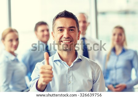 business, teamwork, people, gesture and technology concept - smiling business team showing thumbs up in office - stock photo
