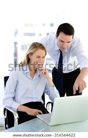 Business teamwork - two business partners working together on laptop at workplace - stock photo