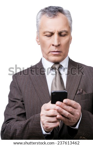 Business technologies. Confident mature man in formalwear holding mobile phone and looking at it while standing against white background