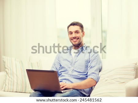 business, technology and e-learning concept - smiling man working with laptop at home