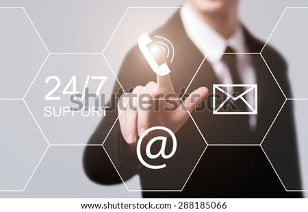 business, technology and internet concept - businessman pressing 24/7 support button on virtual screens - stock photo