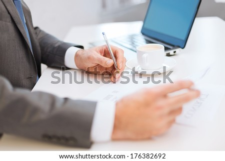 business, technology and internet concept - close up of man hands with contract and pen, coffee and laptop computer - stock photo