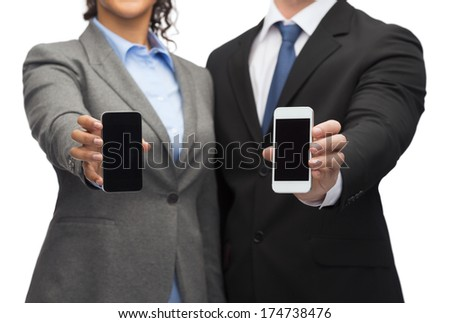 business, technology and internetconcept - businessman and businesswoman with blank black smartphone screens - stock photo