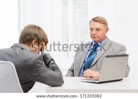 business, technology and office concept - older man and young man having argument in office - stock photo
