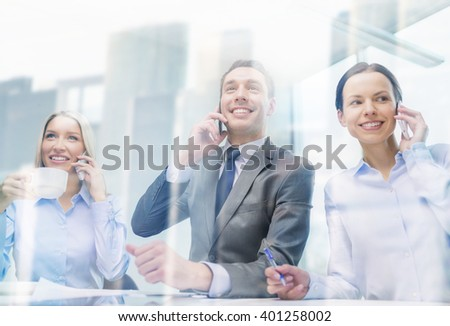 business, technology and office concept - smiling business team with smartphones making calls in office