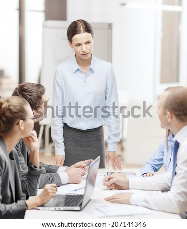 business, technology and office concept - strict female boss talking to business team