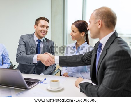 business, technology and office concept - two smiling businessman shaking hands in office - stock photo