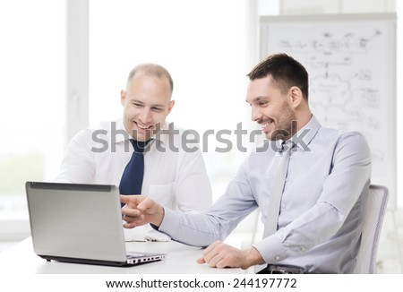 business, technology and office concept - two smiling businessmen with laptop in office - stock photo