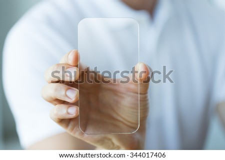 business, technology and people concept - close up of male hand holding and showing transparent smartphone at office - stock photo