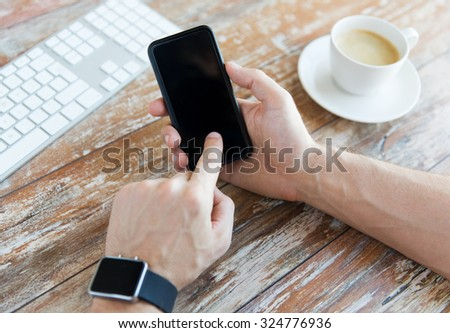 business, technology and people concept - close up of male hand holding smart phone and wearing watch with coffee and keyboard at wooden table - stock photo
