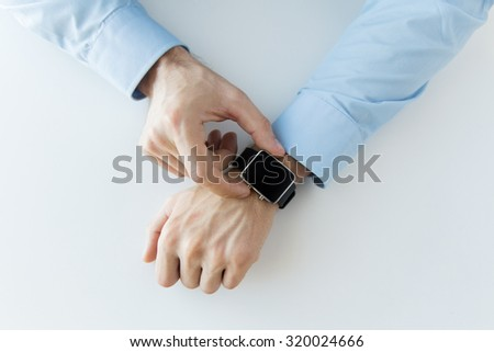 business, technology and people concept - close up of male hands setting smart watch at home - stock photo