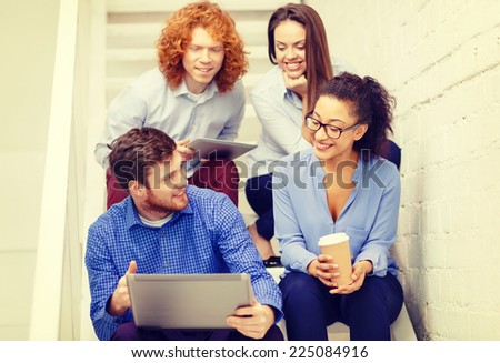 business, technology and startup concept - smiling creative team with laptop and tablet pc computer sitting on staircase