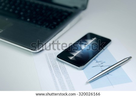 business, technology and statistics concept - close up of smartphone with sound wave or signal diagram on screen, laptop computer and chart with pen on office table