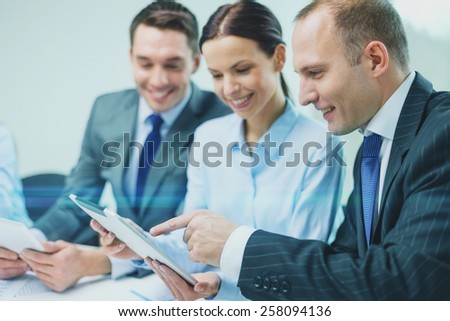 business, technology and teamwork concept - business team with tablet pc computer having discussion in office - stock photo