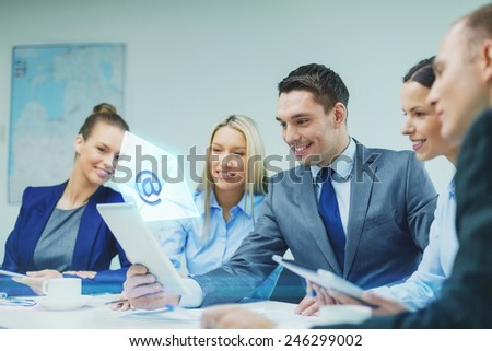 business, technology, communication and people concept - smiling business team with tablet pc computer and virtual message icon projection having discussion in office