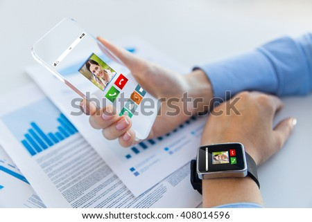 business, technology, communication, connection and people concept - close up of woman hand holding transparent smartphone and smartwatch with incoming call at office