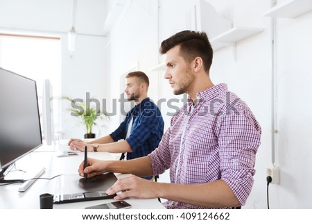 business, technology, design and people concept - young creative man or designer with computer and pen tablet working at office - stock photo