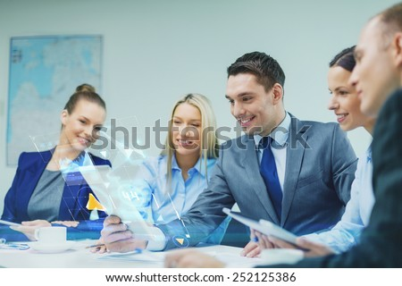 business, technology, development and people concept - smiling business team with tablet pc computer and virtual screen projection having discussion in office - stock photo