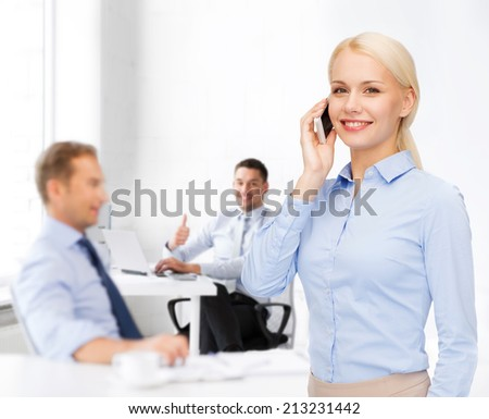 business, technology, education and people concept - smiling young businesswoman with smartphone making call in office