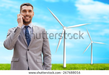 business, technology, innovation, energy saving and people concept - smiling businessman calling on smartphone over windmills and blue sky background