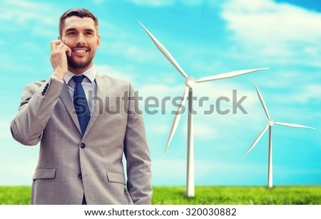 business, technology, innovation, energy saving and people concept - smiling businessman calling on smartphone over windmills and blue sky background - stock photo