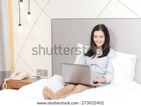 business, technology, internet and hotel concept - happy businesswoman with laptop computer lying in hotel in bed - stock photo