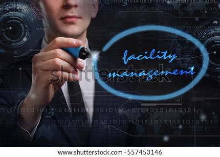 Business, Technology, Internet and network concept. Young business man writing word: facility management