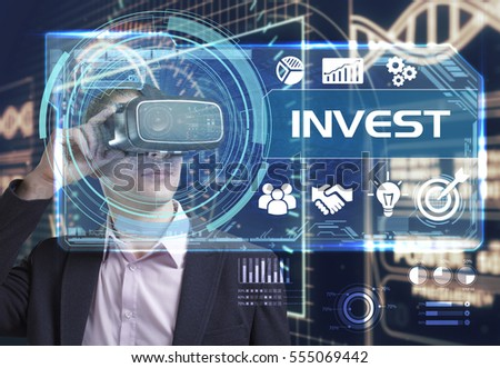 Business, Technology, Internet and network concept. Young businessman working in virtual reality glasses sees the inscription: invest